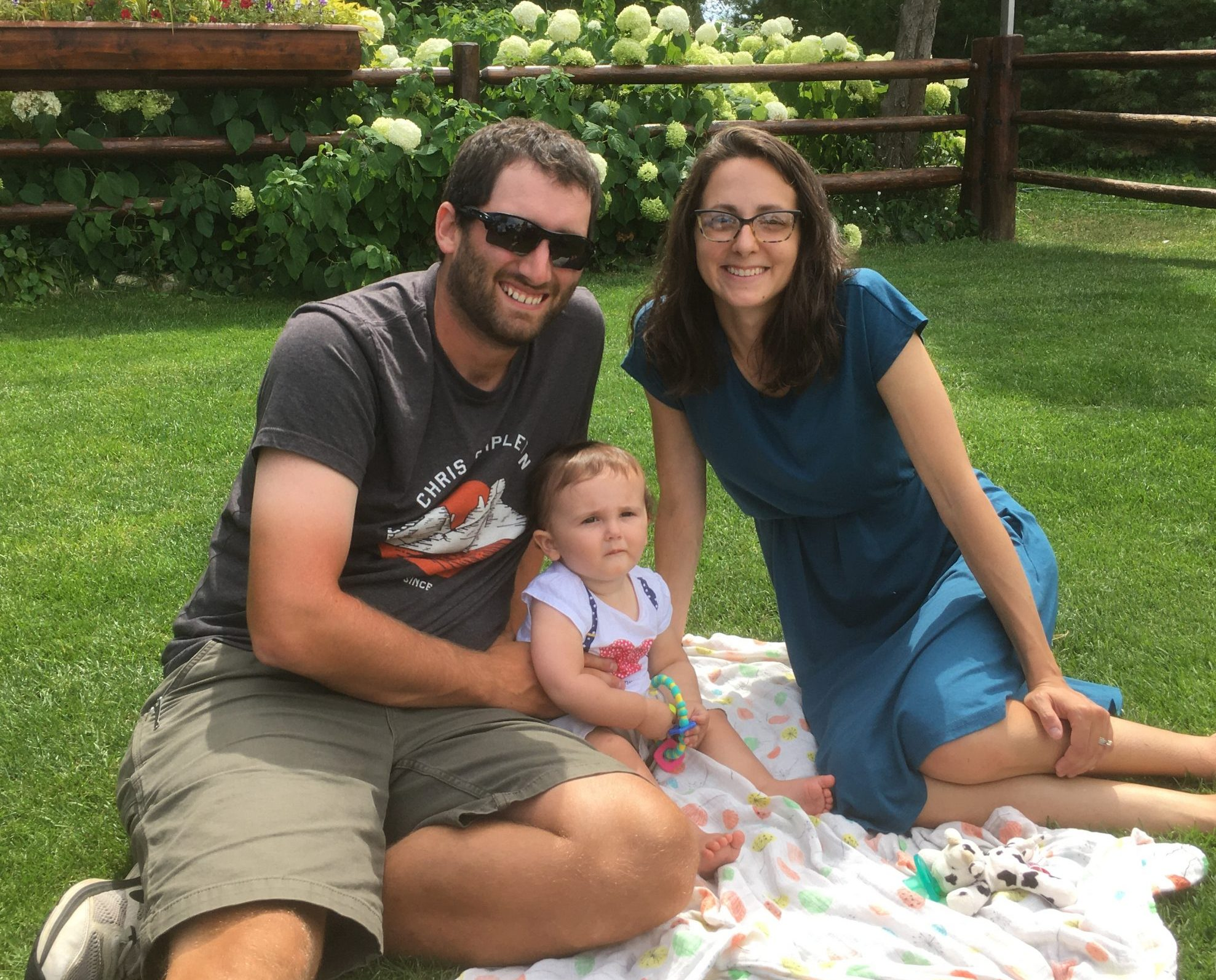family of three on vacation, baby on blanket